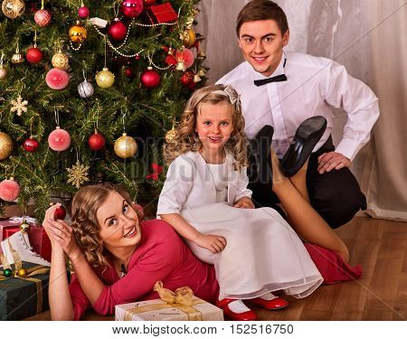 Family with children dressing Christmas tree. Christmas family portrait.