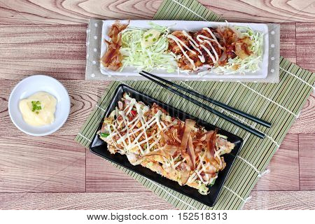 """Japan pizza,""""Okonomiyaki"""",fried mixed vegetable flour with meat and grill flour wrap squid as """"Takoyaki"""",topped sweet sauce ,mayonnaise and sliced dried yellowfin tuna served with side dish. poster"""