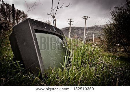 an old abonded tv lying in the gras