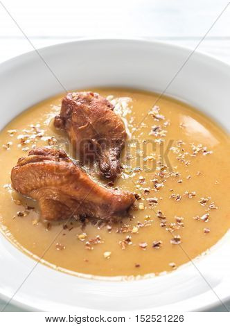 Portion Of Pea Cream Soup With Smoked Chicken Wings