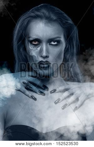Closeup portrait of a pretty gothic woman with hands of vampire on her neck on black background