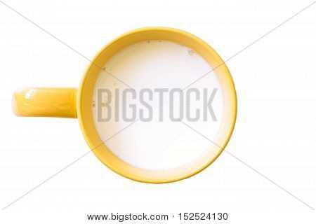 Top view of glass milk yellow and white in simple glass. Isolated on white background. Round copy space in center.