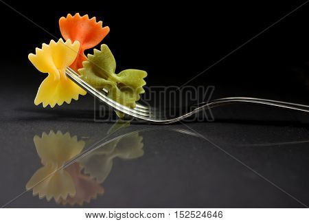 Reflexion of pasta farfalle on a fork