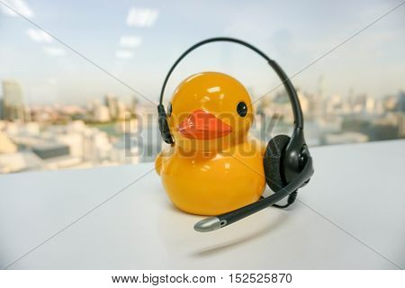 isolated yellow duck callcenter with headset on table
