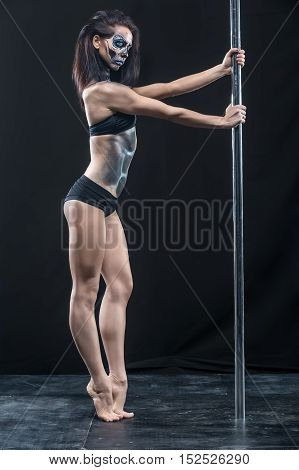 Pretty pole dancer in black sport underwear stands on the toes next to a pylon in the studio on the dark background. She has a body-art on her body. Girl holds her hands on the pylon. Vertical.