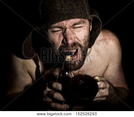 Dark portrait of scary evil sinister bearded man with smirk, he opens a bottle of brandy his teeth . strange Russian man with a naked torso and a woolen hat.
