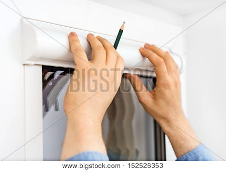Man Installing Cassette Roller Blinds On Windows.