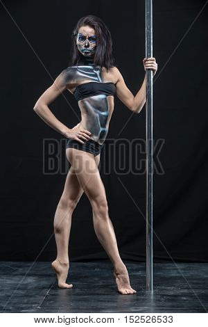 Charming pole dancer in black sport underwear stands on the toes next to a pylon in the studio on the dark background. She has a body-art on her body. Girl looks into the camera. Vertical.
