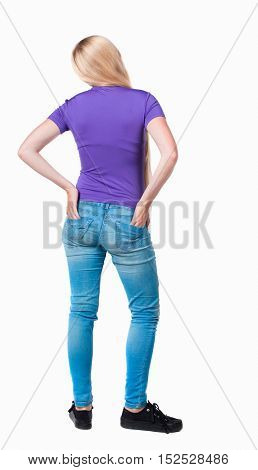 back view of standing young beautiful  woman. girl watching. Rear view people collection.  backside view  person. Long-haired blonde in the purple shirt stands with his hands back pockets his pants