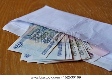 White envelope full of Russian currency (Russian Ruble, RUB) on the wooden table as a symbol of cash transfer, money laundering or bribery in Russia