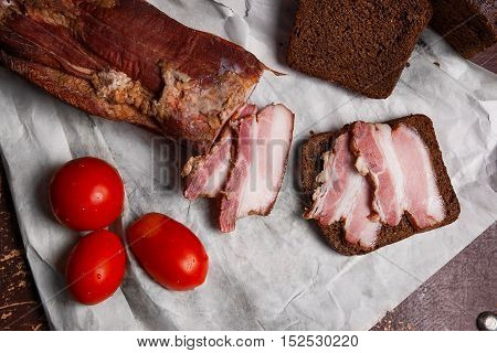 Smoked Bacon With Rye Black Bread And Tomatoes On The Packaging Paper. Vintage Naturmort In A Rustic