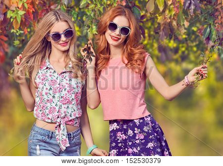 Fall Fashion. Urban Model Woman in Fashion Outfit Having Fun. Glamour Sexy Hipster Girl, fashion Trendy Hairstyle. Sisters Friends Crazy Enjoy Autumn Nature, Stylish Sunglasses. Autumn Outdoor Park