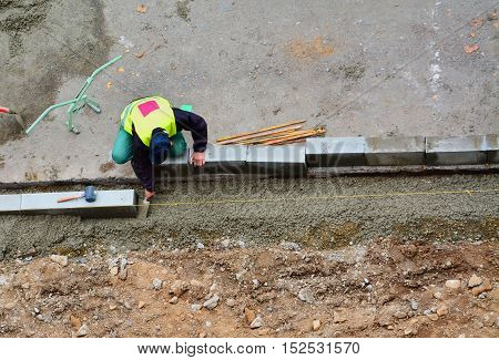 Worker levels the concrete bedding with a trowel for curbs installation. String line is stretched for alignment.