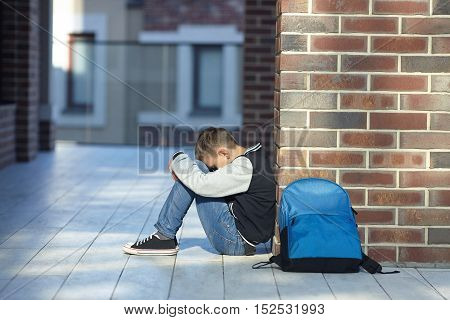 schoolboy crying in the hallway of the school negative emotion