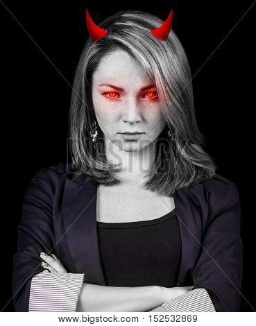 Crazy, angry business woman with red eyes and devil horns over black background