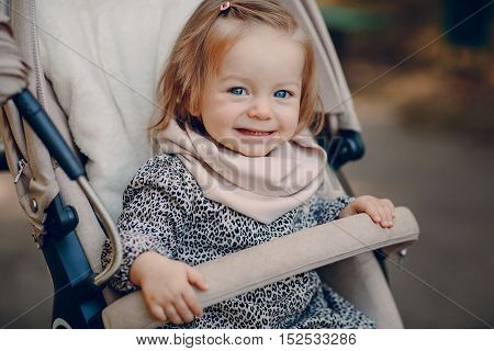 little  and very beautiful girl sitting in the pram and waiting for mom