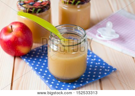 Organic pureed fruits for baby on a wooden background