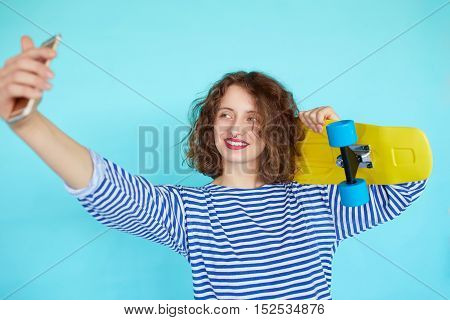 Vivid portrait of hipster pretty cool young woman with skateboard taking self portrait on smartphone over blue background