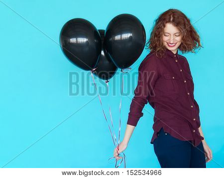 Portrait of cheerful fashion hipster girl with caucasian appearance, standing over blue color wall and holding a bunch of black balloons