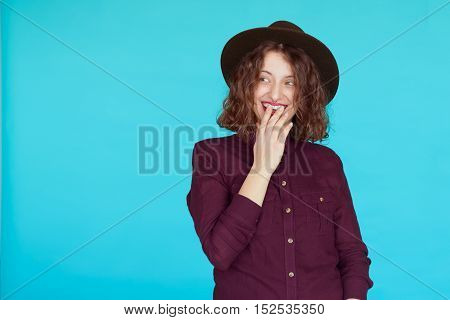 Surprised young woman wearing warm violet shirt and stylish hat over blue turqoise color background with copy space. Excited hipster girl covering her mouth looking to copyspace.