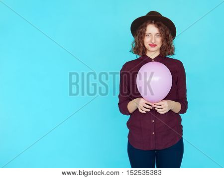 Young redhead woman holding pink balloon isolated over blue turqouise background with copyspace.