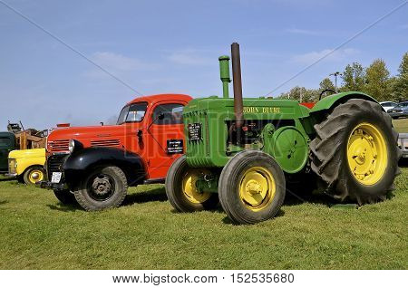 ROLLAG, MINNESOTA, Sept 1. 2016: A restored John Deere tractor and Dodge pickup truck are displayed at the annual WCSTR farm show in Rollag held each Labor Day weekend where 1000's attend.