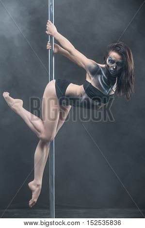 Sexy pole dancer with body-art hangs on a pylon in the studio on the dark background with a cloud of a smoke. She holds the pylon with the hands from the back and looks into the camera. Vertical.