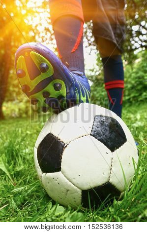 foot with footbal boots on the ball close up photo. Boot on ball.