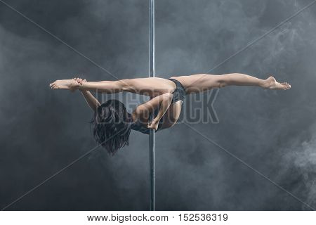 Improbable pole dancer with body-art makes a split while hangs upside down on a pylon in the studio on the dark background with a cloud of a smoke. She wears black sport underwear. Horizontal.