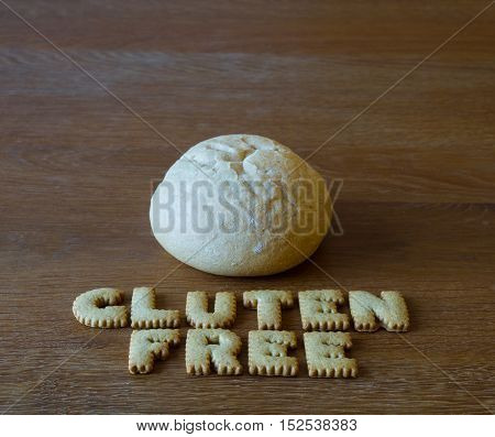 A gluten free bread roll, bap or bun with the phrase Gluten Free spelled out using alphabet shaped cookies on a wooden background.