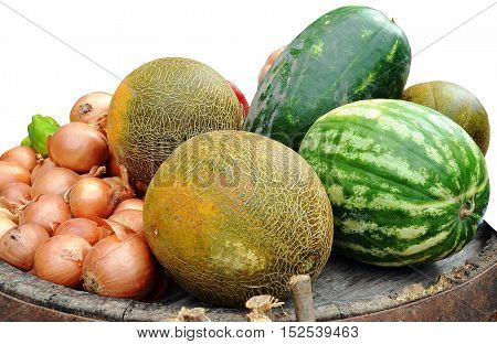 Watermelons, melons, onions, green pepper lie on bottom of upturned wooden barrels. Closeup, isolated on white background