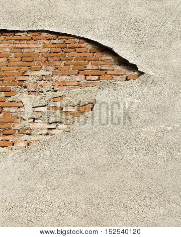 Damaged wall facade with exposed bricks underneath.