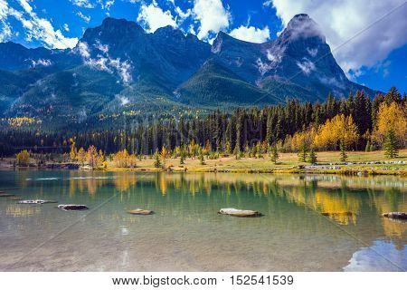Shining day in Canmore. The famous Three Sisters mountains in the Canadian Rockies. Concept of hiking