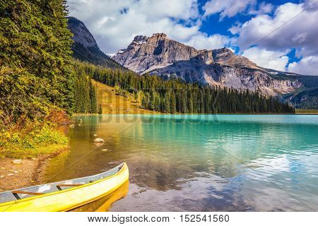 Sunny day in autumn Yoho National Park. In shallow water, the boat is moored. The concept of eco-tourism and active tourism. The mountain Emerald lake