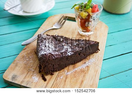 Chocolate cake with fruits salad by a cup of tea