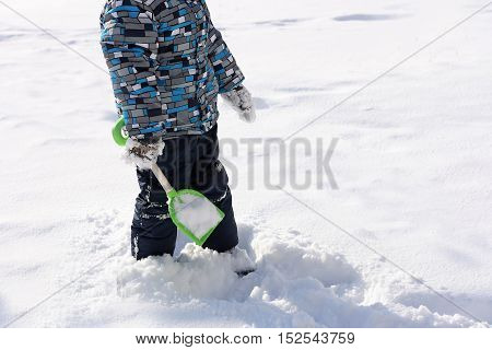 Walking in the fresh air. The image of the child dressed in a warm jacket and pants. A boy stands with a toy shovel in the middle of the snow.
