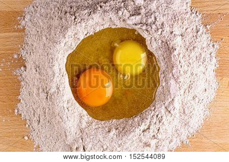 Two Light Yellow and Dark Yellow Egg Yolks into Heap of Whole Wheat Flour closeup on Wooden Table