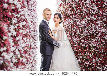 Side view of romantic wedding couple standing amidst red flower decorations