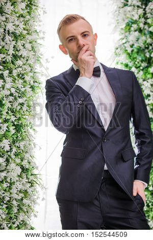 Full length of thoughtful bridegroom standing amidst flower decorations