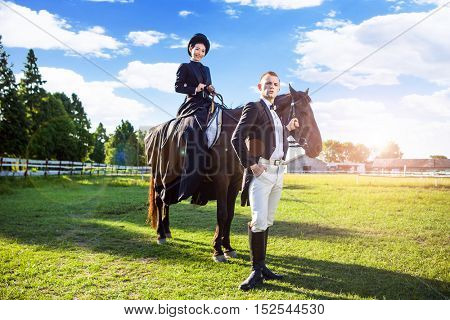 Well dressed man taking care of his girlfriend sitting on a horse in a field