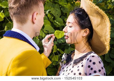 Man tickling womans nose with green leaf