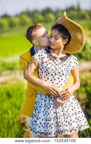 Side view portrait of romantic couple embracing on field