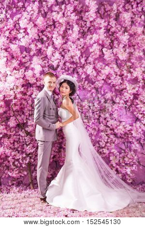 Side view of wedding couple standing against wall covered with pink flowers
