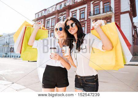 Pretty young women with shopping bags having fun walking on the street