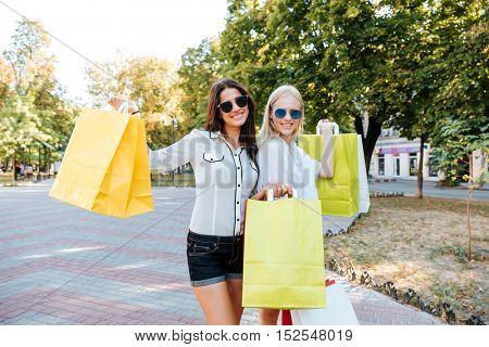 Two beautiful young women with shopping bags walking in the ctiy