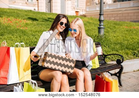 Two women sitting outside looking at pretty shoes they've just purchased