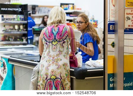 CYPRUS, PROTARAS, SUPERMARKET BEST BUY - 14 OCTOBER 2016: Woman is standing at the cash register and paying for the goods