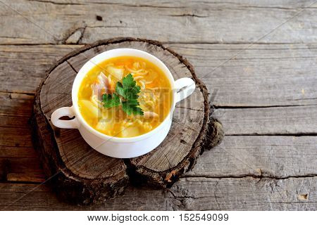 Homemade chicken noodle soup in a bowl. Soup cooked in chicken broth with potatoes, noodles, onions and carrots. Old wooden background with blank space for text