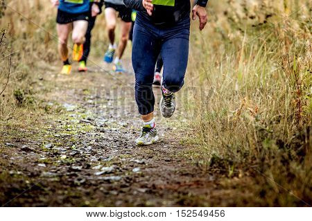 group runners running uphill in autumn trail of mud and stones