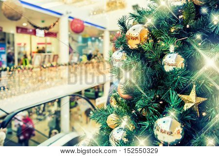 Christmas tree with gold decoration in shopping mall.Christmas clearance sales at the shopping mall. Elegant Christmas tree in a shopping mall.